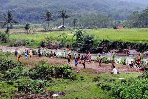 Sejumlah anak bermain sepak bola di lahan kosong bantaran sungai Cileungsi, Sukamakmur, Kabupaten Bogor, Jawa Barat, Rabu (22/3). - Antara/Yulius Satria Wijaya
