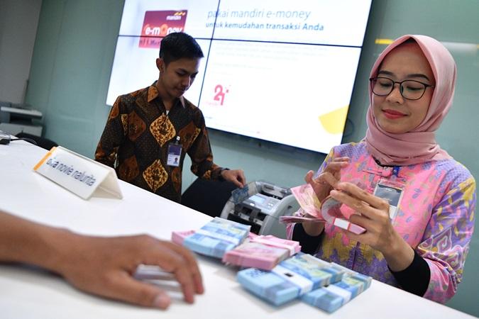 Karyawan melayani nasabah di Bank Mandiri Cabang Plaza Mandiri, Jakarta, Rabu (2/10/2019). - ANTARA FOTO/Sigid Kurniawan