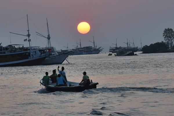 Wisatawan mengabadikan matahari tenggelam di perairan Labuan Bajo, Manggarai Barat, Nusa Tenggara Timur, Jumat (12/10/2018). - ANTARA/Indrianto Eko Suwarso