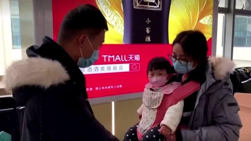 Keluarga mengenakan masker, termasuk anak-anak di  stasiun kereta di Provinsi Hubei China, 22 Januari 2020. - Reuters
