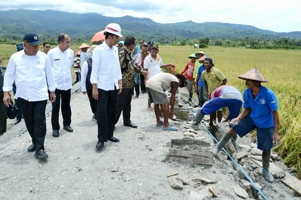 Presiden Joko Widodo (ketiga kiri) didampingi Menteri PUPR Basuki Hadimuljono (kiri) meninjau pembangunan irigasi dan jalan produksi persawahan di Desa Waimital, Kecamatan Kairatu, Kabupaten Seram Bagian Barat, Maluku, Rabu (14/2/2018). - BPMI Setpres