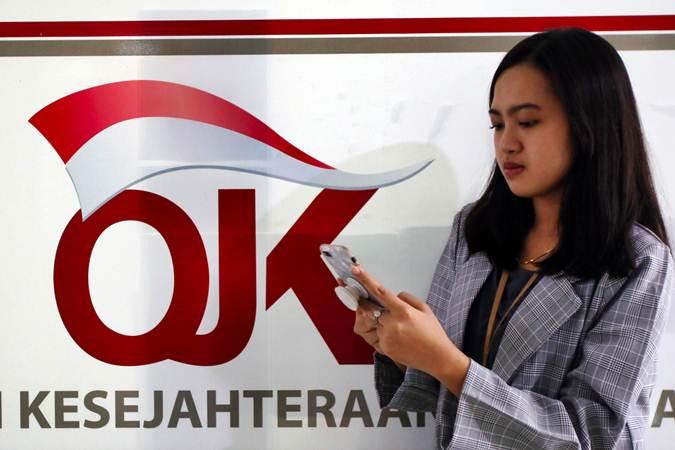 Karyawan melintas di dekat logo Otoritas Jasa Keuangan (OJK) di Jakarta - Bisnis/Abdullah Azzam