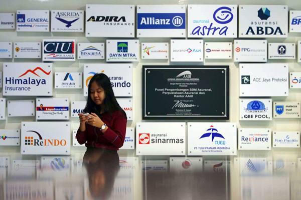 Karyawan berdiri di dekat logo beberapa perusahaan asuransi di kantor Asosiasi Asuransi Umum Indonesia (AAUI) di Jakarta, Selasa (21/2/2017). - JIBI/Nurul Hidayat