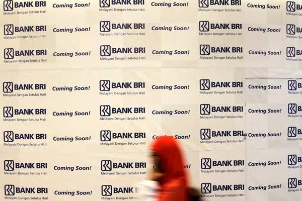 Pengunjung melintasi logo Bank BRI di sebuah pusat perbelanjaan di Jakarta, Senin (13/4/2018). - Bisnis.com