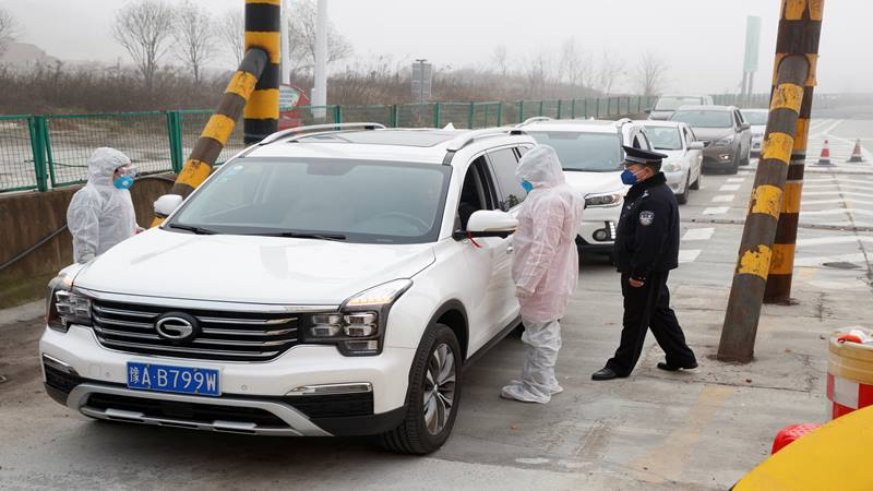 Petugas medis mengenakan pakaian pelindung memeriksa suhu tubuh penumpang mobil di sebuah pos pemeriksaan di luar Kota Yueyang, Provinsi Hunan, dekat perbatasan dengan Provinsi Hubei yang sedang diisolasi setelah wabah virus corona baru, China, 28 Januari 2020. - Reuters
