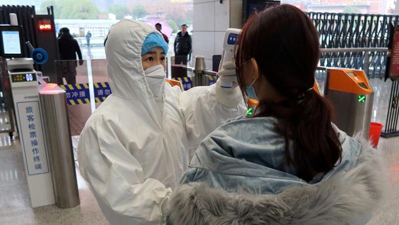 Ilustrasi. Seorang petugas berjas pelindung memeriksa suhu seorang penumpang yang tiba di Stasiun Xianning Utara, di Xianning, sebuah kota yang berbatasan dengan Wuhan di utara, di provinsi Hubei, China 24 Januari 2020. - REUTERS / Martin Pollard