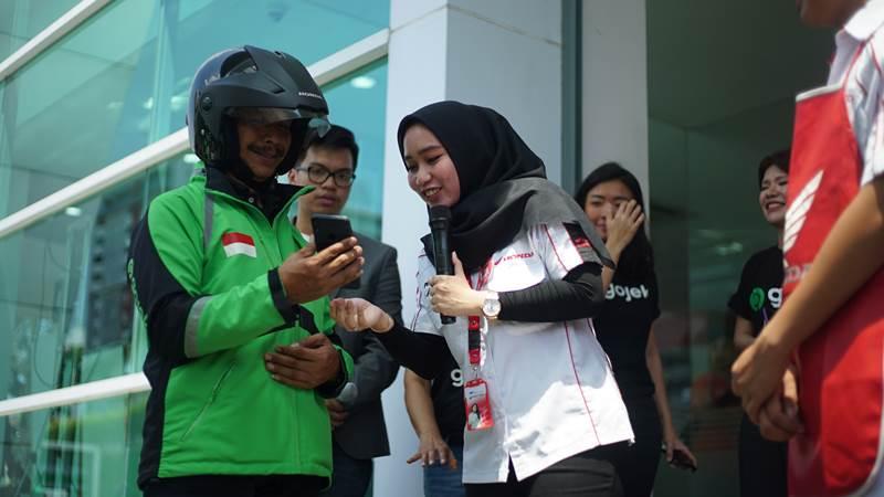 Driver Gojek (kiri) menunjukkan identitas kepada petugas layanan servis Astra motor - Bisnis/Alif Nazzala Rizqi