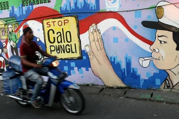 Warga melintas di dekat dinding lukisan mural bertuliskan imbauan stop calo pungutan liar di Kantor Pelayanan SIM Mapolres Metro Bekasi Kota, di Bekasi, Jawa Barat, Rabu (24/7/2019). - Antara