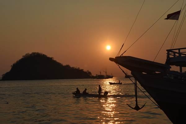 Nelayan melintas saat matahari tenggelam di perairan Labuan Bajo, Manggarai Barat, Nusa Tenggara Timur, Jumat (12/10/2018). - ANTARA/Indrianto Eko Suwarso