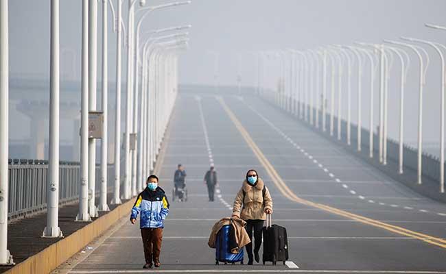 Warga tiba dari Provinsi Hubei saat melintasi pos pemeriksaan di Jembatan Sungai Jiujiang Yangtze di Jiujiang, Provinsi Jiangxi, China, Jumat (31/1/2020). Reuters - Thomas Peter
