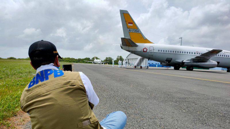 Petugas BNPB memotret pesawat TNI yang membawa WNI dari Wuhan China, di Natuna, Minggu. - Antara/Cherman.