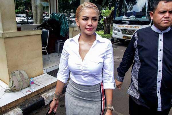 Artis Nikita Mirzani memasuki gedung saat akan menjalani pemeriksaan di Ditreskrimsus Unit Cyber Polda Metro Jaya, Jakarta, Senin (26/2). - ANTARA/Rivan Awal Lingga