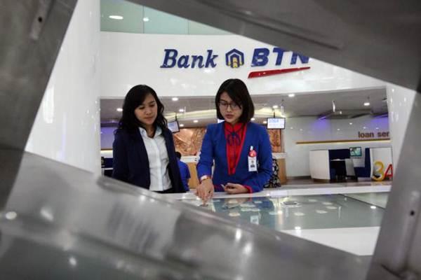 Karyawati PT Bank Tabungan Negara Tbk memberikan penjelasan mengenai produk perbankan kepada nasabah di Jakarta, Senin (8/1). - JIBI/Dedi Gunawan
