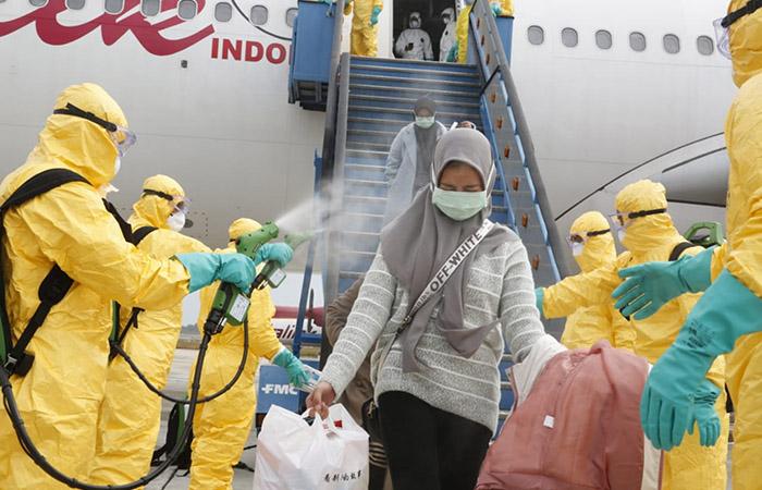 Petugas medis menyemprotkan cairan disinfektan pada Warga Negara Indonesia (WNI) dari Wuhan, China setibanya di Bandara Hang Nadim, Batam, Kepulauan Riau, Minggu (2/2/2020). Antara Foto - Kementerian Luar Negeri RI
