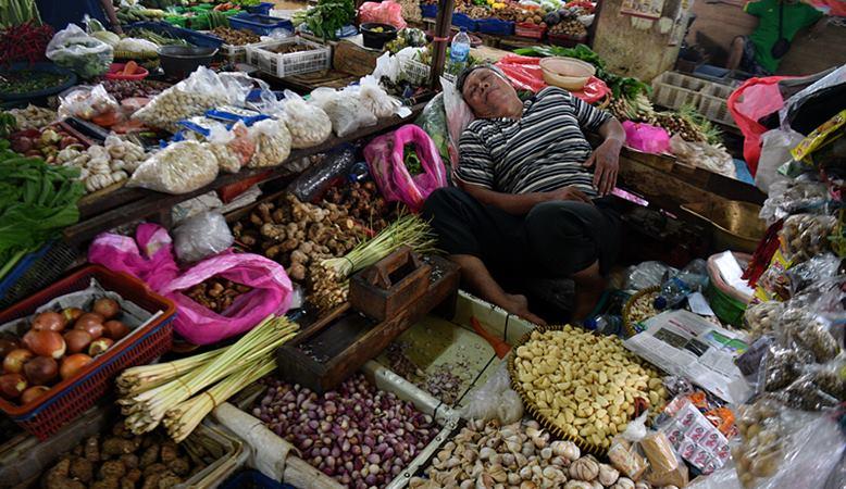 Pedagang aneka bahan bumbu masakan tertidur saat menunggu calon pembeli di Pasar Minggu, Jakarta Selatan, Senin (27/1/2020). -  ANTARA / Sigid Kurniawan