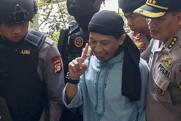 Terdakwa kasus dugaan terorisme Oman Rochman alias Aman Abdurrahman (tengah) dikawal polisi seusai menjalani sidang pembacaan vonis di Pengadilan Negeri Jakarta Selatan, Jakarta, Jumat (22/6/2018). Majelis hakim memvonis Aman Abdurrahman dengan hukuman mati. - ANTARA/Galih Pradipta