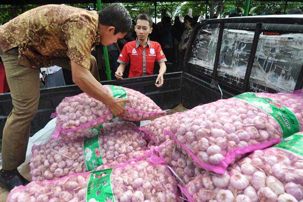 Petugas menurunkan bawang putih milik Bulog dari mobil pengangkut untuk dipasarkan pada pasar murah yang digelar di Palu, Sulawesi Tengah, Selasa (13/6). - Antara/Mohamad Hamzah