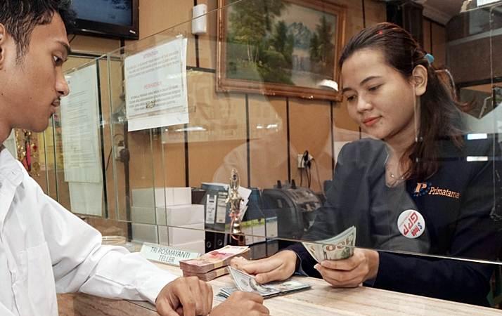 Karyawati sebuah Money Changer melayani penukaran uang, di Jakarta, Rabu (12/6/2019). - Bisnis/Himawan L. Nugraha