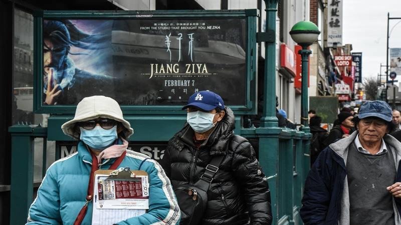 Pejalan kaki memakai masker wajah berjalan di sepanjang jalan di lingkungan Flushing di Queens Borough, New York, AS, pada hari Rabu, 5 Februari 2020. - Bloomberg