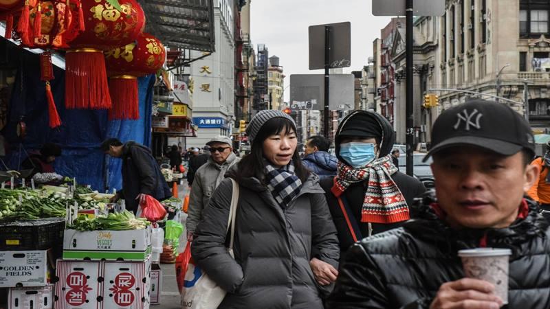 Seorang pejalan kaki mengenakan masker wajah berjalan di sepanjang jalan di lingkungan Flushing di Queens Borough, New York, AS, pada hari Rabu, 5 Februari 2020.  - Bloomberg
