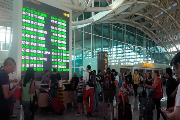 Penumpang mencari informasi di layanan customer sercive Bandar Udara I Gusti Ngurah Rai - Bisnis.com/Feri Kristianto