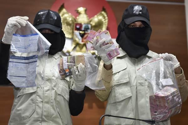 Ilustrasi-Penyidik KPK memperlihatkan barang bukti uang hasil operasi tangkap tangan - ANTARA/Hafidz Mubarak A