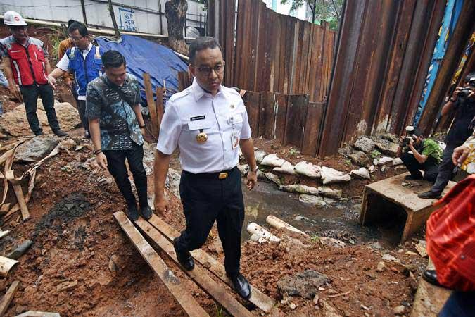 Gubernur DKI Jakarta Anies Baswedan (tengah) saat meninjau titik banjir yang bersebelahan dengan proyek LRT di Underpass Cawang, Jakarta, Kamis (4/4/2019). - ANTARA/Indrianto Eko Suwarso