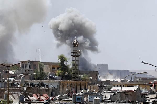 Asap mengepul dari posisi militan Negara Islam (IS) setelah serangan artileri oleh pasukan Irak di Mosul barat, Irak pada 18 Juni 2017. REUTERS  -  Erik De Castro