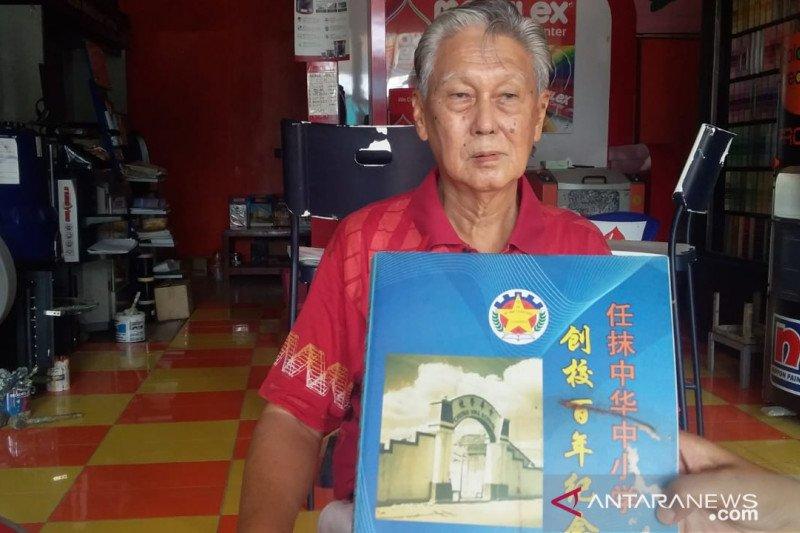 Salah satu guru Chung Hua School Jember Chen Yong Yen atau Iwan Natawidjaja saat menunjukkan buku kenangan sekolah Tionghoa Jember di tokonya di Jember pada Kamis (6/2/2020) (ANTARA -  Zumrotun Solichah)