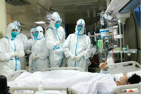 Seorang pasien 2019-nCoV di Rumah Sakit Hankou, Wuhan, memberikan isyarat jempol kepada tim kesehatan dari Second Military Medical University, Senin (27/1/2020). - Antara