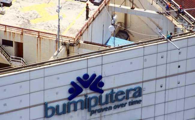 Pekerja beraktivitas di dekat logo Asuransi Jiwa Bersama (AJB) Bumiputera 1912, Jakarta, Rabu (29/1 - 2020).