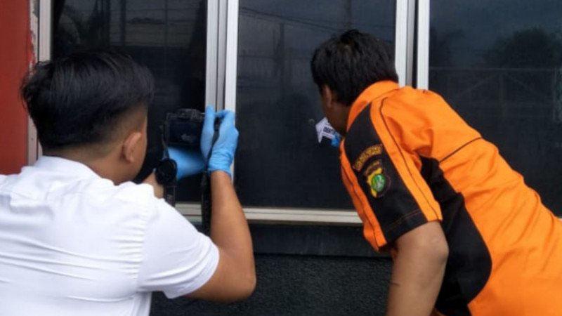 Petugas Satuan Reserse Kriminal Polrestro Jakarta Timur memeriksa lubang di kaca ruang pelayanan administrasi Rutan Klas 1 Cipinang, Jakarta Timur, yang ditembak oleh orang tidak dikenal, Senin (10/2/2020)./Atara - Andi Firdaus)