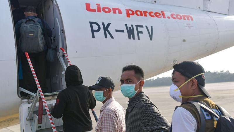 Penumpang maskapai Wings Air menggunakan masker saat akan menaiki pesawat di Bandara Hang Nadim, Batam, Selasa (4/2/2020). - Antara/ M Risyal Hidayat