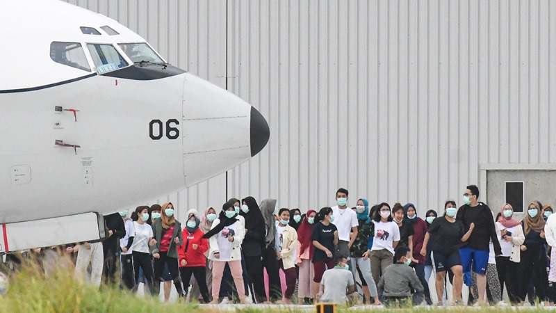 Sejumlah Warga Negara Indonesia (WNI) yang dievakuasi dari Wuhan, Hubei, China melakukan senam bersama prajurit TNI pada hari kesembilan di Hanggar Pangkalan Udara TNI AU Raden Sadjad, Ranai, Natuna, Kepulauan Riau, Senin (10/2/2020). -  ANTARA / M Risyal Hidayat