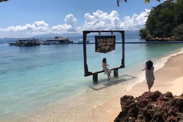 Turis China pengunjung Pulau Gangga, Sulawesi Utara, berfoto di spot yang telah disiapkan oleh pengelola, Kamis (30/1/2020). - Bisnis/M. Nurhadi Pratomo