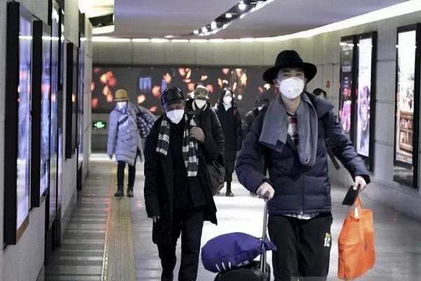 Seorang perempuan menggunakan masker saat berjalan bersama rekannya di Chinatown di wilayah Manchester, Inggris, Senin (27/1/2020). - Reuters