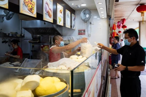 Warga mengenakan masker sebagai bentuk pencegahan atas virus corona, di area Chinatown di Singapura, Senin (10/2/2020). - Bloomberg/Seong Joon Cho