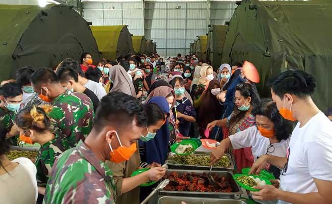 Sejumlah Warga Negara Indonesia (WNI) yang dievakuasi dari Wuhan, China mengambil makan di pusat observasi di Hanggar Pangkalan Udara TNI AU Raden Sadjad, Ranai, Natuna, Kepulauan Riau, Rabu (12/2/2020). ANTARA FOTO - PUSPEN TNI