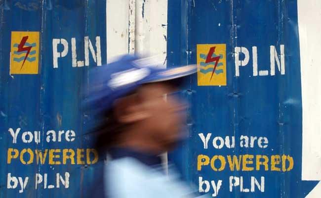 Warga melintas di dekat logo Perusahaan Listrik Negara (PLN) di Jakarta, Rabu (12/2/2020). Bisnis - Himawan L Nugraha