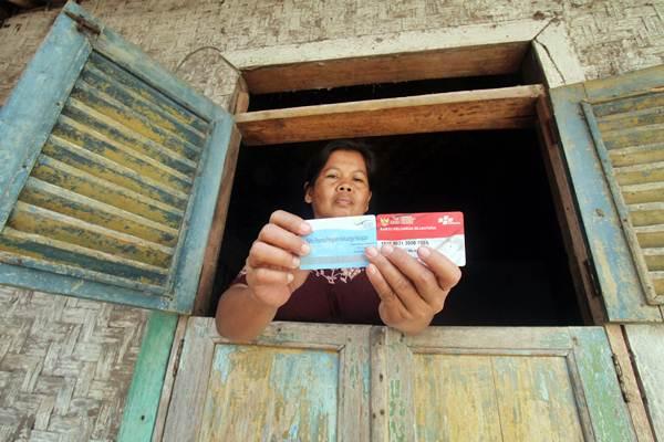 Warga menunjukan kartu peserta Program Keluarga Harapan (PKH) di Desa Gunung Sari, Citeureup, Bogor, Jawa Barat - ANTARA/Yulius Satria Wijaya