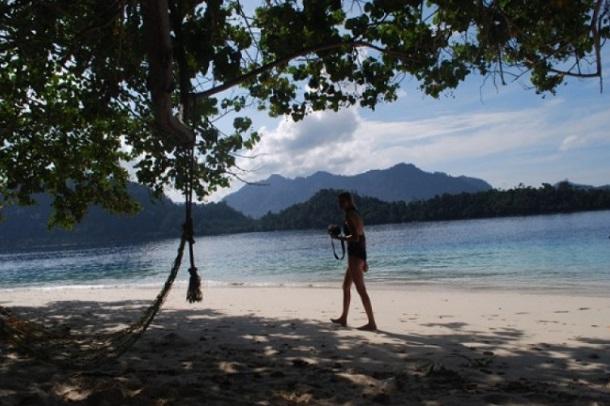 Seorang turis melintas bertelanjang kaki di atas pasir putih Pulau Pagang. - Antara