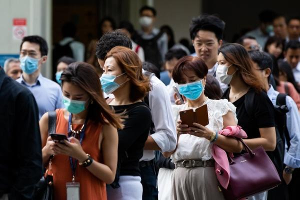 Warga mengenakan masker sebagai bentuk pencegahan atas virus corona, di kawasan pusat bisnis Singapura, Senin (10/2/2020). - Bloomberg/Seong Joon Cho