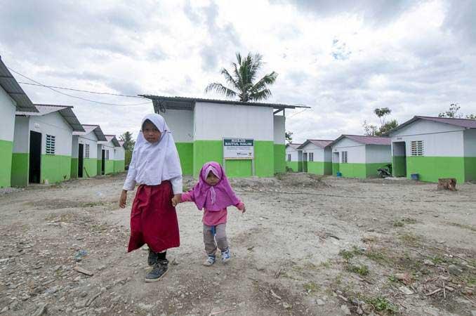 Dua orang anak korban gempa melintas di depan kompleks Hunian Sementara (Huntara) di Desa Baliase, Sigi, Sulawesi Tengah, Kamis (14/3/2019). - ANTARA/Basri Marzuki