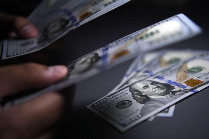 Seorang pembeli menghitung uang Dolar Amerika Serikat yang ditukarnya di gerai penukaran valuta asing, Jakarta, Senin (15/7/2019). - ANTARA - Puspa Perwitasari
