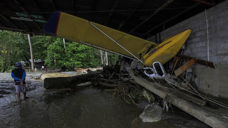 Warga berada di dekat pesawat udara yang terdampak banjir bandang di Sentani, Kabupaten Jayapura, Papua, Minggu (17/3/2019). Berdasarkan data BNPB, banjir bandang yang terjadi pada Sabtu (16/3/2019) tersebut mengakibatkan 63 orang meninggal dunia. - Antara