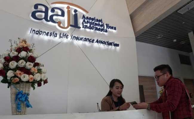 ryawan beraktivitas di dekat logo asuransi jiwa di Jakarta, Selasa (28/1/2020). Bisnis - Himawan L Nugraha