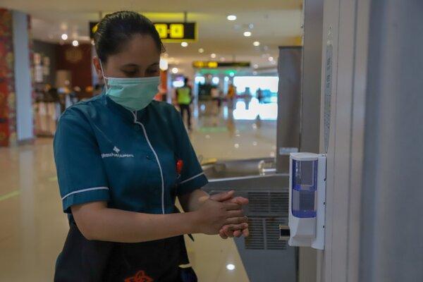 Pengunjung Bandara I Gusti Ngurah Rai saat menggunakan cairan pembersih tangan atau hand sanitizer yang disediakan manajemen Angkasa Pura I dengan tujuan utama pencegahan serta antisipasi potensi penyebaran Virus Corona ke Bali. - Istimewa