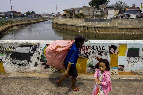 Warga beraktivitas di kawasan Sungai Ciliwung, Jakarta, Jumat (14/9/2018). - ANTARA/Galih Pradipta