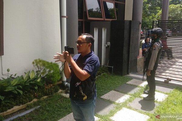 Wartawan mengambil gambar sementara petugas keamanan bersenjata laras panjang berjaga di pintu gerbang masuk kompleks perkantoran DPRD Tulungagung, Senin (17/2/2020). - Antara/Destyan Handri Sujarwoko