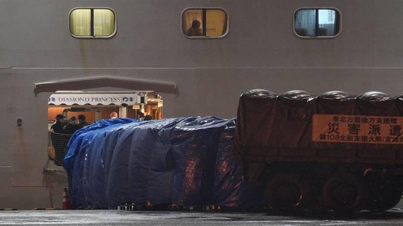 Pekerja mengenakan pakaian pelindung berdiri di pintu masuk kapal pesiar Diamond Princess, yang dioperasikan oleh Carnival Corp, berlabuh di Yokohama, Jepang, pada hari Minggu, 16 Februari 2020. Lebih dari 300 orang warga Amerika Serikat (AS) yang menjadi penumpang kapal itu kembali ke rumah. - Bloomberg